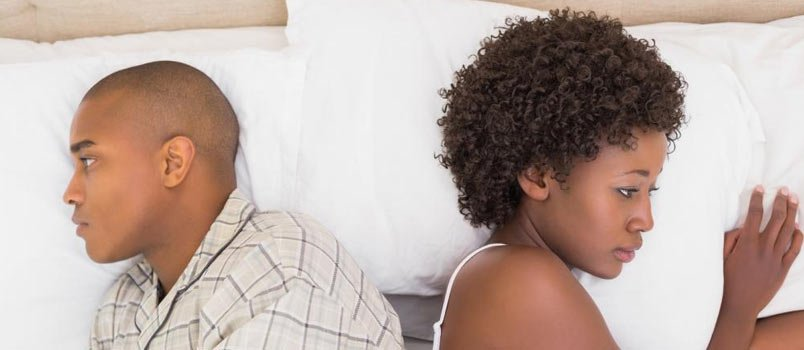 man and woman angry on bed away from each other