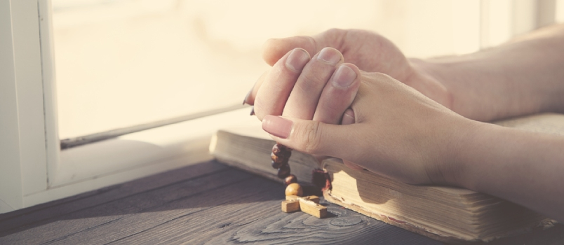 Cross On The Couple Hands On Wooden Background