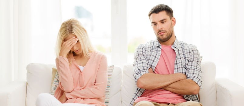 Sad Break Couple Seated Together On Couch At Home