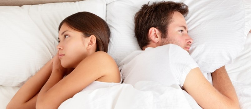 Man and woman facing opposite sides in bed after a fight