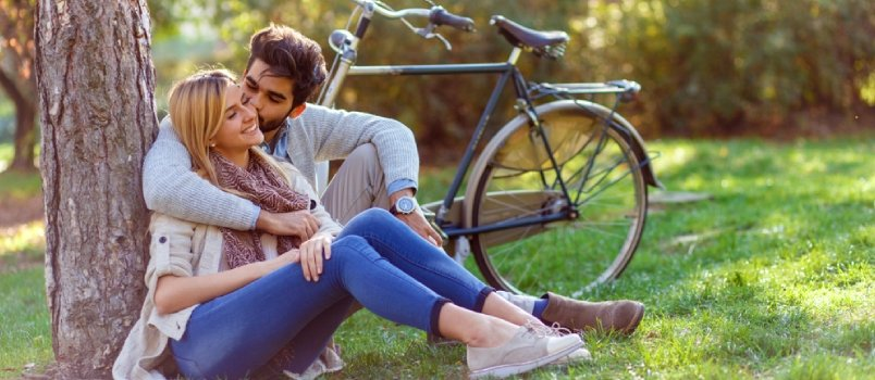 Man kissing woman on cheek while they both sit in nature