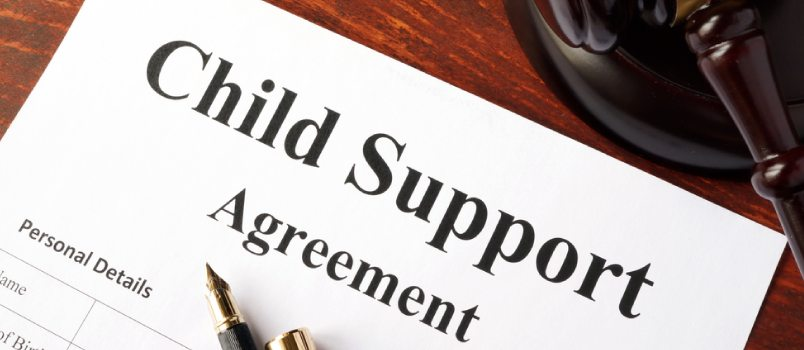 Child support agreement sitting on desk with pen on top