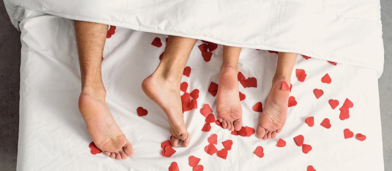 Couple legs cover with white bed sheet