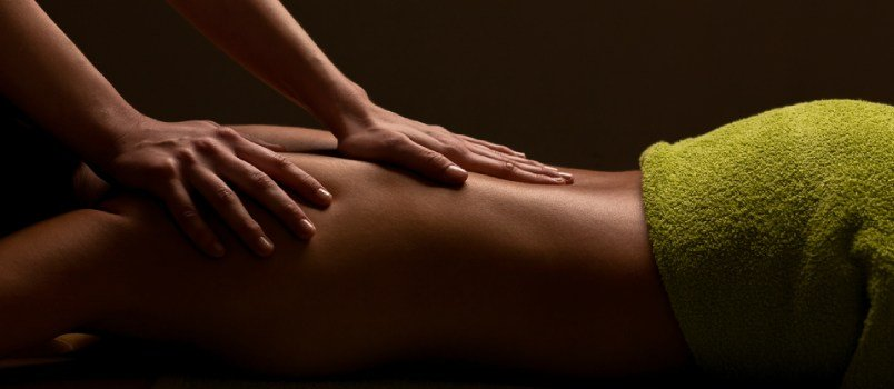 Find a massage therapy centre and see if they'll send  2 massage therapists to your house