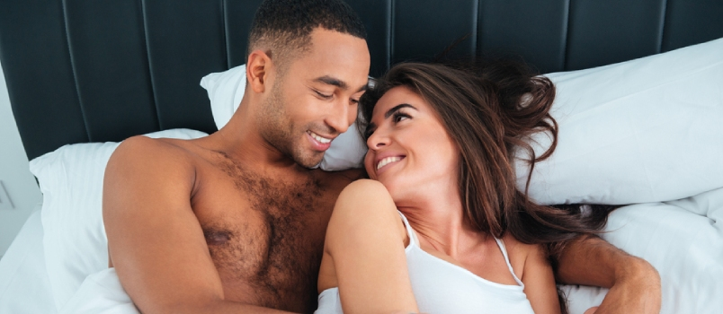 Happy Young Couple Lying In Bed And Looking At Each Other