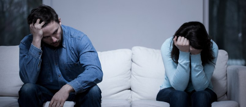 Upset Couple Sitting On Couch Head Down Conflict Relationship Concept