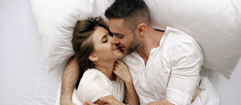 Young Beautiful and Loving Couple Kiss and Hug Into Bed