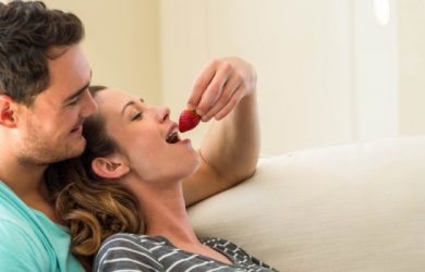 Man Feeding A Strawberry To Woman In Living Room