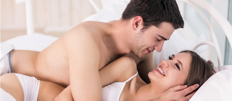 Beautiful Young Loving Couple Lying In Bed And Looking At Each Other