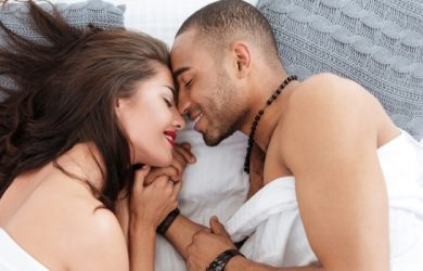 Young Romantic Couple Hugging And Kissing, Laying Down On A White Bed