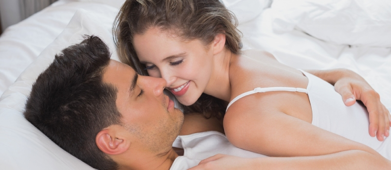 Romantic Young Couple In Bed At Home Girl Smiling