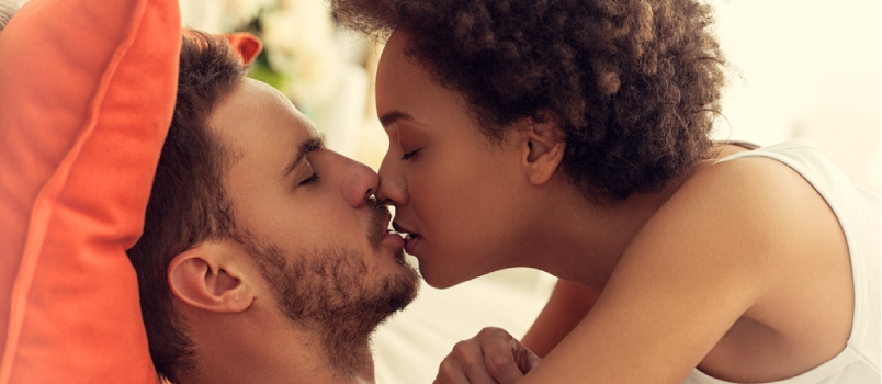 Mixed-race African And American Couple Kissing In Bed