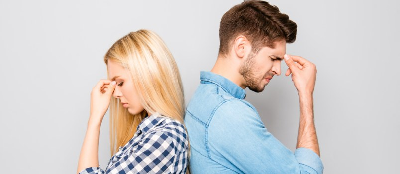 Young Depressed Couple Standing Back To Back, Hand On Head Upset Moment