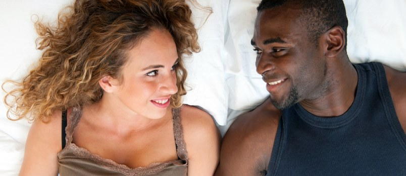 African Couple Laying On Bad