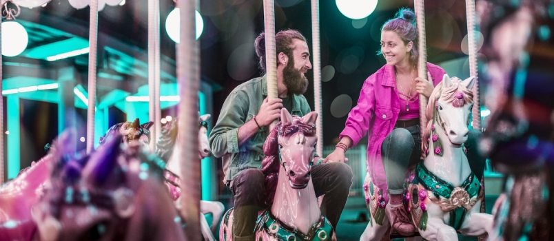 Beautiful Couple Riding A Carousel Smiling And Happy