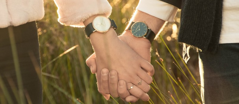 Woman And Man Hand-holding In The Grassy Field