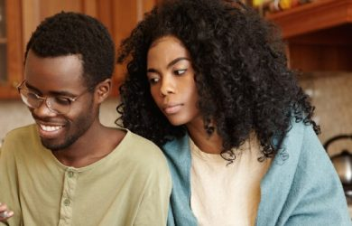 Handsome Dark Skinned Boy Using Smartphone And Suspicious Wife Spying On Him