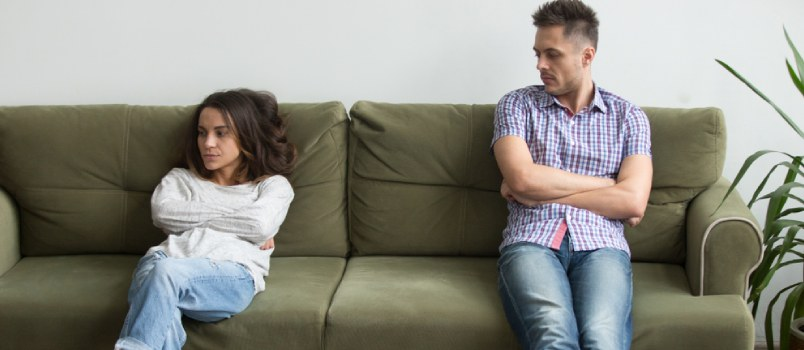Frustrated Couple Sit Apart On Couch In Living Room