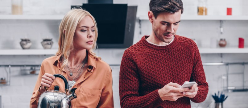 Jealous young woman with kettle looking at husband with smartphone in kitchen