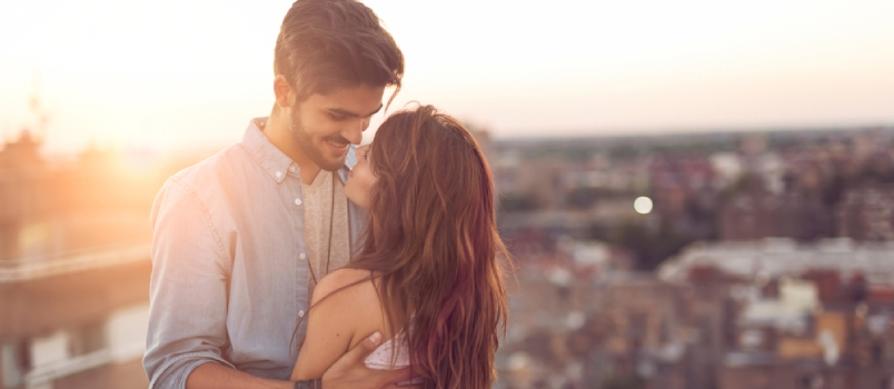 Couple In Love Standing And Hugging On A Building Rooftop At Sunset