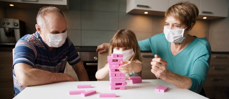 Old Age Man And Women Playing Game With Masking With A Little Girl