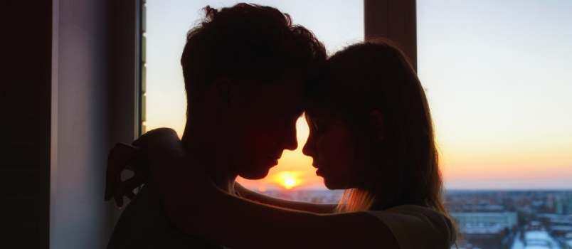 Couple In Love, Profile Silhouettes Close To Each Other, Beautiful Sunset In Window At Background