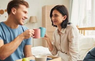 Happy Young Couple Enjoying Breakfast In Bed And Clinking Coffee Mugs