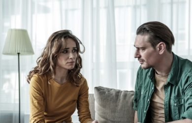 Upset Couple Is Sitting On Sofa And Looking At Each Other Pensively
