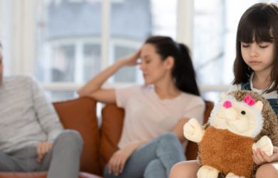 Little Upset Unhappy Girl Sitting On Couch At Home Separately From Arguing Parents