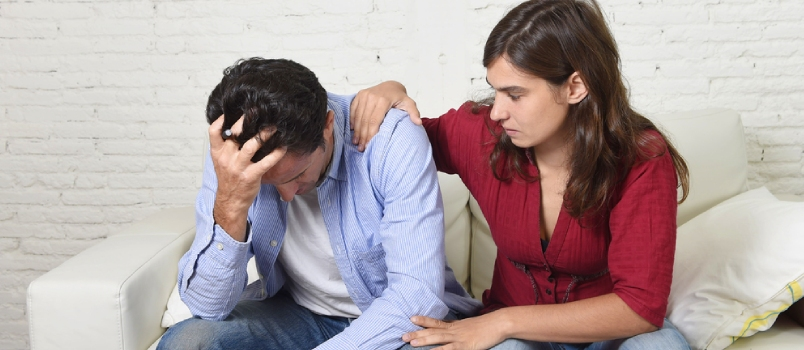 Young Couple Worried Home In Stress Wife Comforting Husband