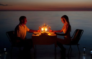 Loving Couple Share A Romantic Dinner With Candles And Lanterns Light Way At Sea Beach