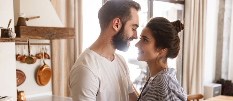 Couple In Love Man And Woman Smiling While Hugging Together In Apartment