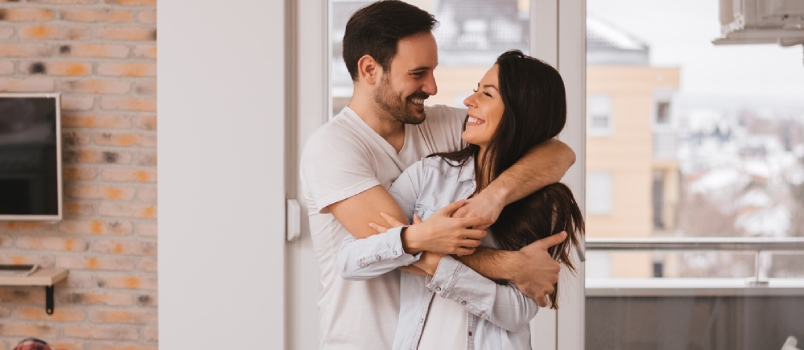 Beautiful Young Couple Hugging In Their New Apartment