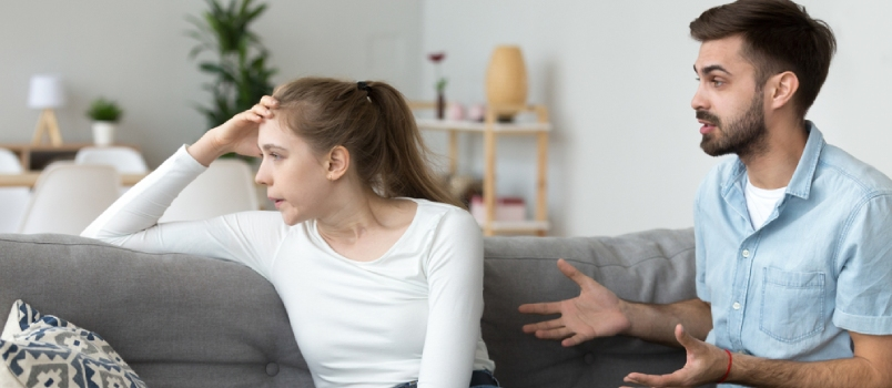 Unhappy Young Millennial Married Couple Sitting On Couch In Living Room