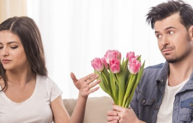 Young Man Is Offering A Bunch Of Flowers To His Angry Girlfriend At Home