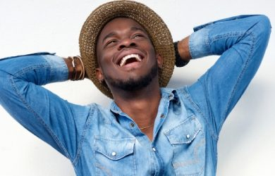Close Up Portrait Of A Young Man Laughing With Hands Behind Head On White Background
