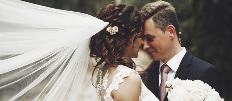 Groom Hugs Bride Tender While Wind Blows Her Veil Somewhere