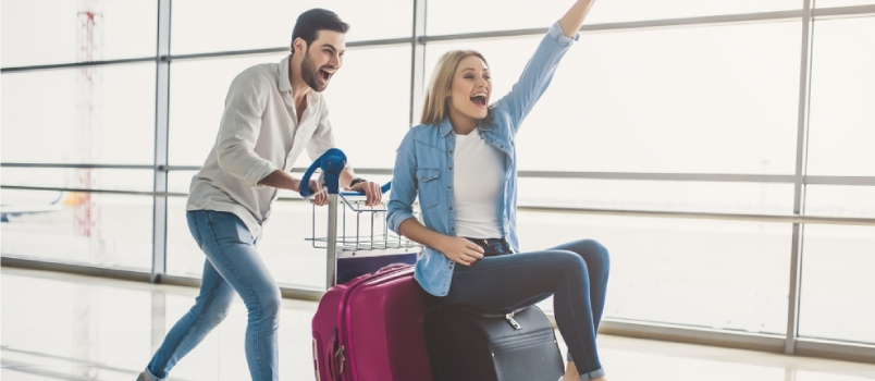 Romantic Couple In Airport With Suitcases Are Ready For Traveling Having Fun On Luggage Trolley