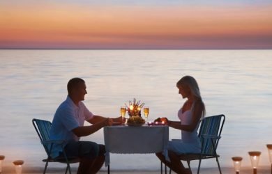 Loving Couple Share A Romantic Dinner With Candles Lanterns And Wine Glasses At Sea Beach Sand Against Wonderful Sunset