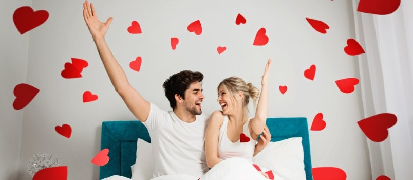 Young Happy Couple Sitting On The Bed Throwing Red Hearts Paper