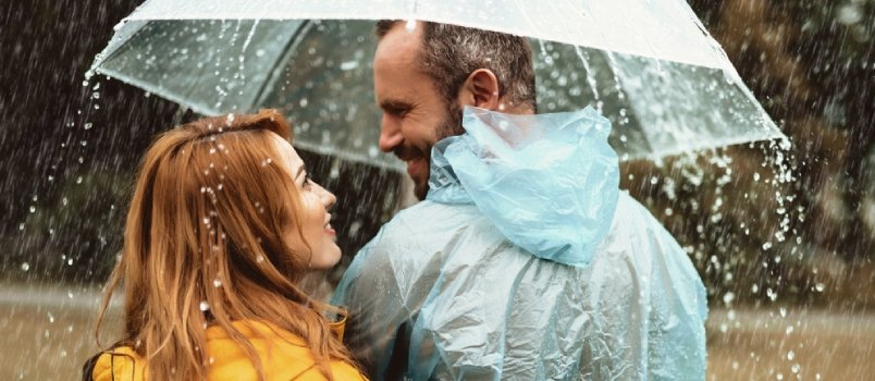 Joyful Man Strolling With Woman In Rain They Are Looking At Each Other With Content And Love