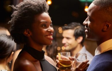 American African Couple Enjoying Party With A Wine Glass And Smiling To Looking At Each Other In Love Concept
