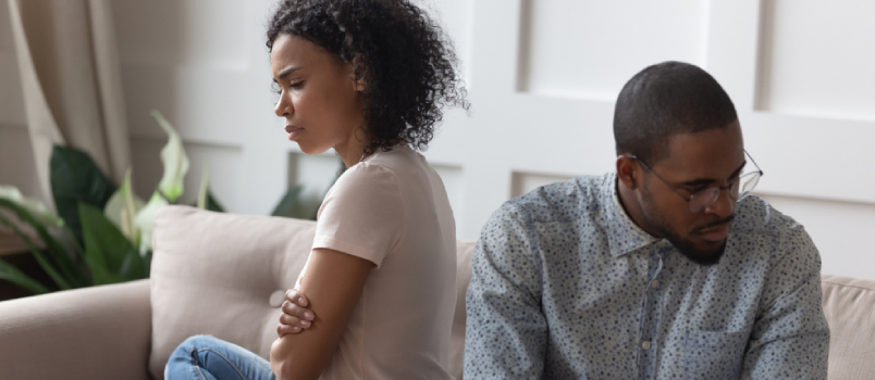 Upset Depressed African American Married Couple Sitting On Sofa With Crossed Hands At Silence After Emotional Quarrel