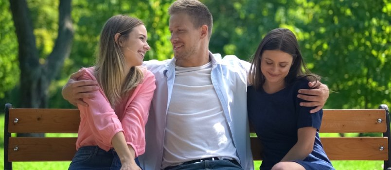 Handsome Man Resting On Bench In Park Hugging Two Attractive Females