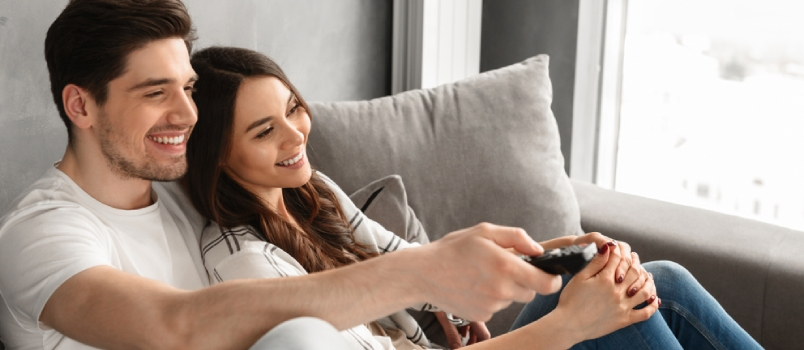 Image Of Happy Man And Woman Sitting On Sofa At Home And Watching Television With Remote Control In Hand