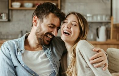 Couple Laugh Together At Home