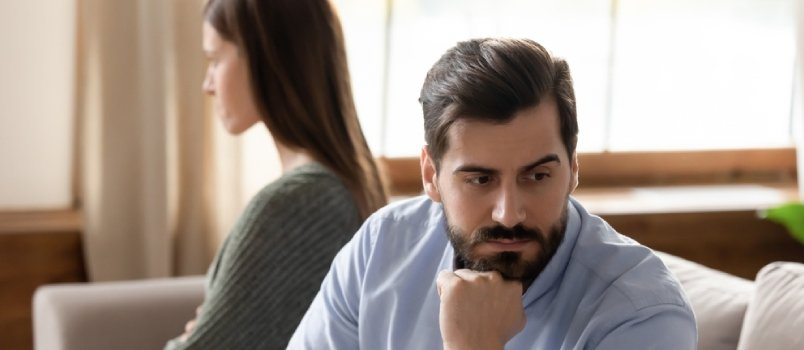 Focus On Stressed Thoughtful Young Man Sitting Separate From Offended Wife On Couch At Home
