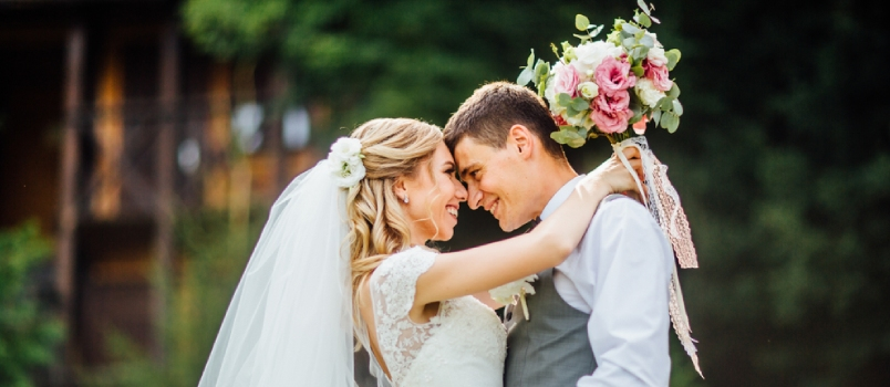 Newlyweds Couple In Love Looks One-on-one With Flowers