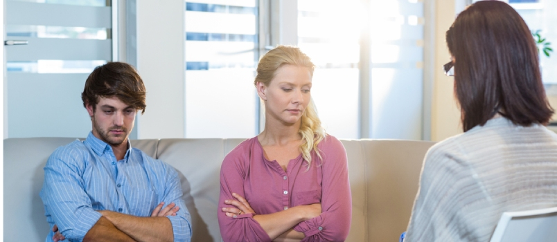 Unsmiling Couple Sitting On The Couch In Therapist Office