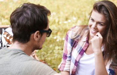 Couple Smiling And Gossip Together On Picnic In The Park